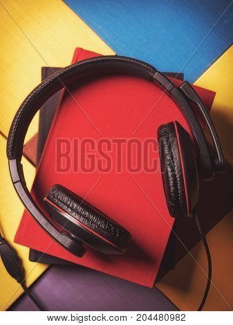 Concept of audiobook. Books on the table with headphones lying on them