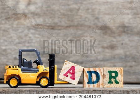 Yellow plastic forklift hold letter A to complete word ADR (Abbreviation of Adverse drug reaction) on wood background