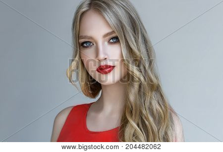 Beautiful  blonde model  girl  with long curly  hair . Hairstyle wavy curls . Red  lips ,  Fashion , beauty and make up portrait