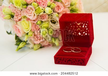 Gold Wedding Ring, A Red Box And A Flower Bouquet Of The Bride