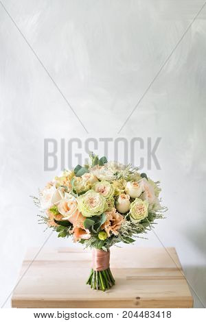 Close-up floral composition with roses and mix flowers on a gray background. caramel-cream gamma. copy space
