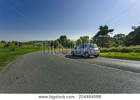 Asphalt Road With Cars Passing Through The Fields In The Region Of Normandy, France. Landscape In Sp