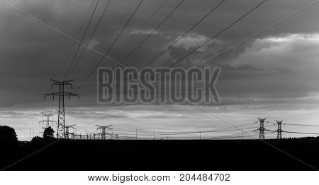 High Voltage Power Lines And Transmission Towers At Sunset. Poles And Overhead Lines Silhouettes. El