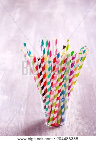 Colored striped drink straws in glass on table