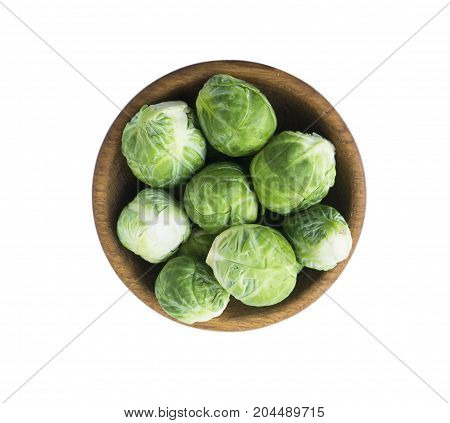 Brussels sprouts cabbage in wooden bowl. Top view. Brussels sprouts cabbage isolated on a white background. Cabbage with copy space for text.