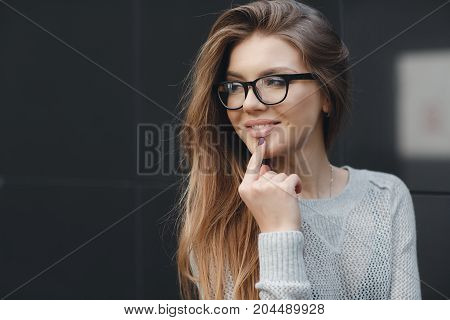 Young beautiful woman with long fair-haired hair,light make-up and sweet smile, wearing glasses in black frame, wearing a knitted pullover of light gray color, posing alone, standing on a dark gray background near the wall, in the fresh air in spring