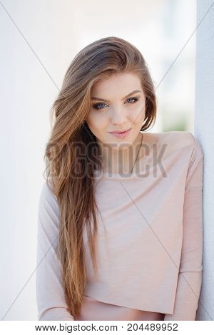 Young beautiful woman with long brown hair, light make-up and cute smile, blue eyes dressed in jewelry, dressed in knitted pullovers of light pink color, posing odin, sitting in front of white background outdoor spring