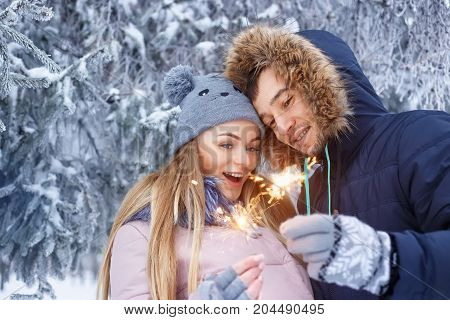 young couple with sparklers in winter forest. Smiling family with bengal lights. Happy smiling couple with holiday sparklers celebrating Christmas outdoors. People, winter, holidays, outdoors concept