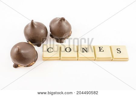 Three cones filled with dulce de leche and bathed in chocolate.''Cones'' written with chips. White background.