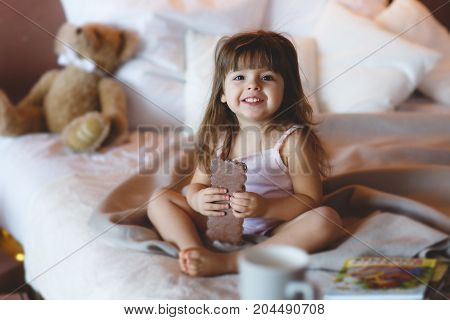 Happy little girl 3 years old,brunette with long hair and straight bangs,a nice smile and brown eyes sitting on white bed in the bedroom, cross-legged amid the pile of white pillows with a huge bar of chocolate in hand,next to a Teddy bear