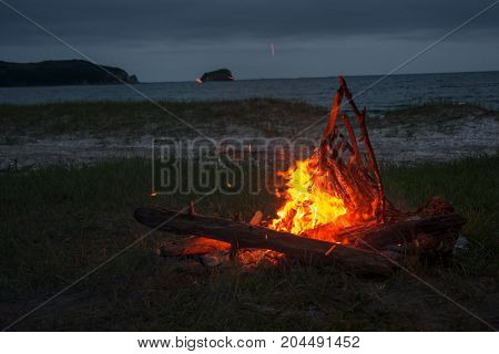 fire burning on the beach at night. bright fire, firewood. flame overnight