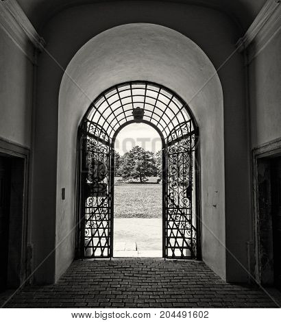 Forged gate and castle park in background Valtice southern Moravia Czech republic. Travel destination. Black and white photo.