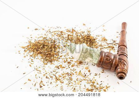 Wood pipe tobacco and dollars. Concept of money. White background.