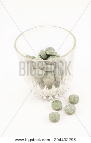 Glass cup with spirulina pills containing vitamin B12 inside. White background. Vertical.