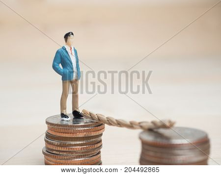 Money and Business Concept. Businessman small figure standing on top of stack of coins and looking forward to the next coins stack with ladder between that.