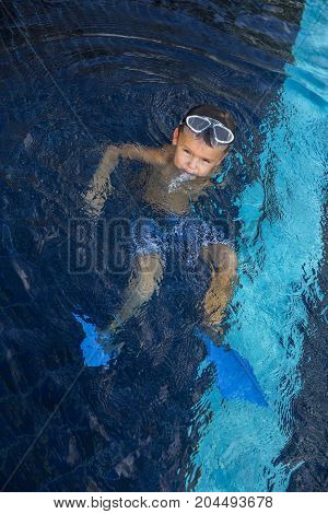 Little child with goggles swimming in the water