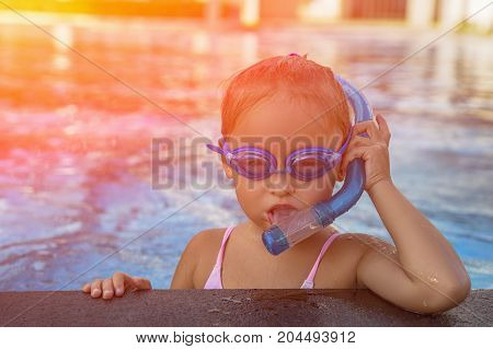 A happy young girl relaxing on the side of a swimming pool wearing goggles and snorkel. Toned