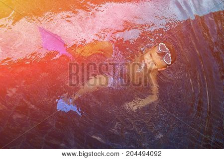 Little child with goggles swimming in the water. Toned