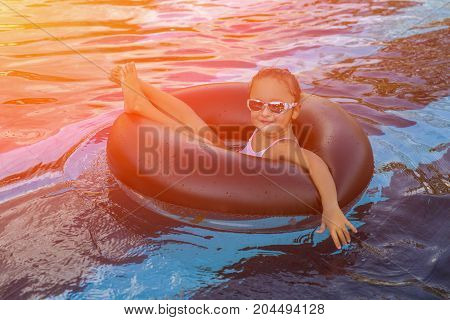 Happy little girl playing with inflatable ring in outdoor swimming pool on hot summer day. Kids learn to swim. Child water toys. Children play in tropical resort. Family beach vacation. Toned