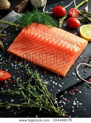Fresh raw salmon fillet steak with aromatic herbs, spices.