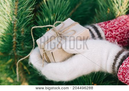 Girl Hands In White Woollen Mittens Holding A Gift Box