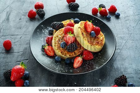 British Crumpets breakfast with blueberries, strawberries, blackberries, raspberries drizzled with icing sugar.