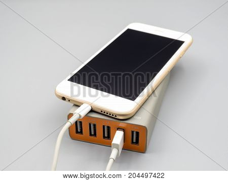 Smart phone charging with multiport USB power adaptor on gray background Selective focus