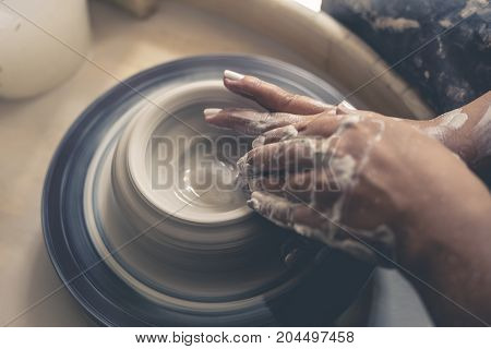 Dirty potter hands works with clay on pottery wheel, toned