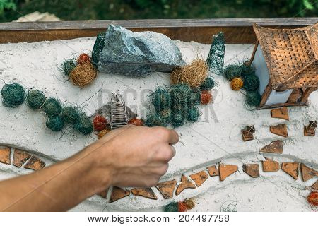 Sand therapy. Man arranges with his hand toy miniature trees and small houses in a sand box. Anti-stress psychological rehabilitation therapy