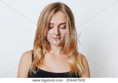 Portrait Of Young Appealing Blonde Female Looks Pensively Down, Wears Casual Clothes, Thinks About R