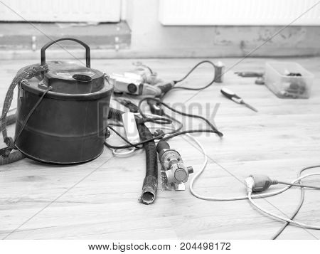 Vacuum cleaner and work tools on the floor black and white photo