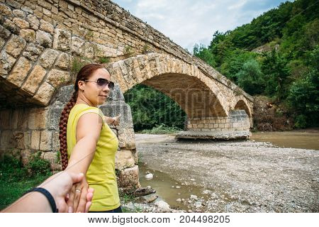Young girl traveler leads man by hand to ancient bridge, follow me concept