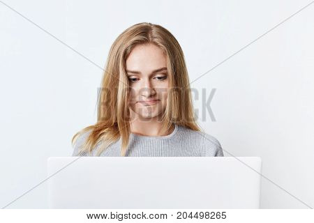Pretty Female Blogger Sits In Front Of Opened Laptop, Writes New Post, Uses High-speed Internet Conn