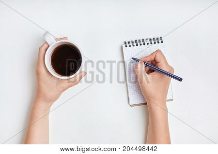 Top View Of Female Hand Writes In Spiral Notebook, Takes Notes With Cup Of Tea. Woman Writes In Her