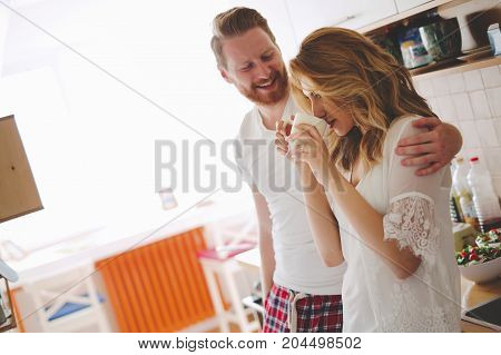Beautiful couple in love having fun being romantic in kitchen