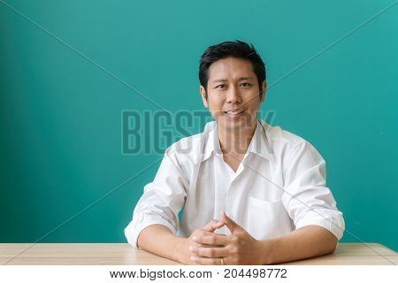 Working with pleasure. Portrait of asian businessman smiling and looking at camera with smile while sitting at his working place of blue wall. Vintage filtered image.