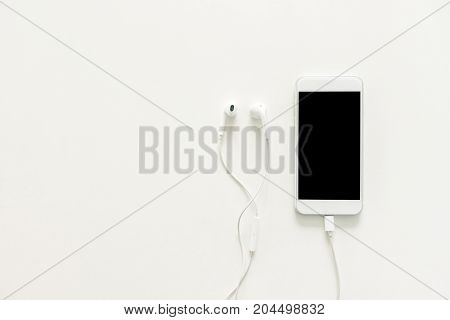 Minimal work space - Creative flat lay photo of workspace desk with earphones and mobile phone with blank screen on copy space white background. Top view mock up flat lay photography.