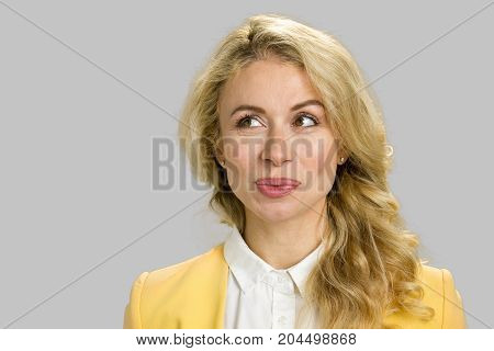Young pretty girl close up. Beautiful young woman in formal wear looking away. Isolated on grey background
