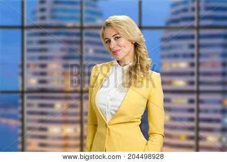 Beautiful blond business woman. Attractive young business woman in yellow jacket standing on evening office background.