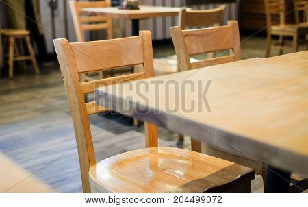 Many brown wooden chairs and table set on wooden floor at coffee shop for background or texture - interior concept.