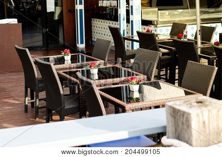 Many black rattan chairs with red rose in vase and clear table set on wooden floor at restaurant for street food background or texture - outdoor concept.