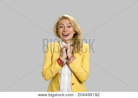 Young woman looking happy and excited. Excited young happy woman holding clasped hands looking in shock on grey background.
