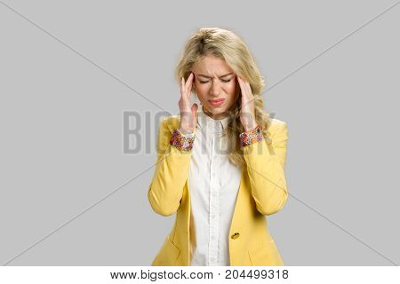 Young woman suffering from headache. Portrait of depressed young blond woman with terrible headache touching temples over grey background.