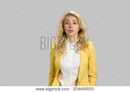 Confused young woman, grey background. Portrait of amusing confused young woman with long blond hair over grey background.