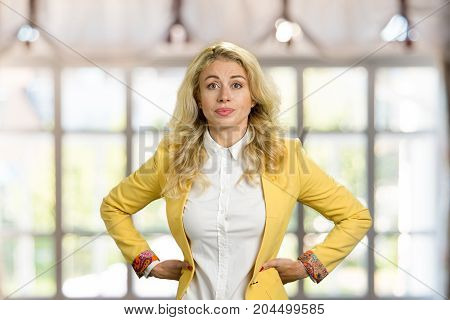Serious young blonde holding hands on hips. Confident young business woman posing with hands on hips on blurred background.
