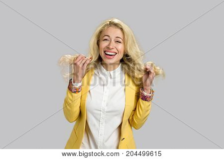 Cheerful happy positive young lady. Smiling blond young woman holding her hair and laughing isolated on grey background.