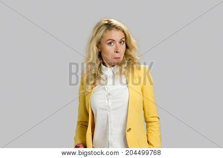 Surprised astonished funny young woman. Closeup portrait blonde woman looking surprised in with wide open eyes isolated on grey background.