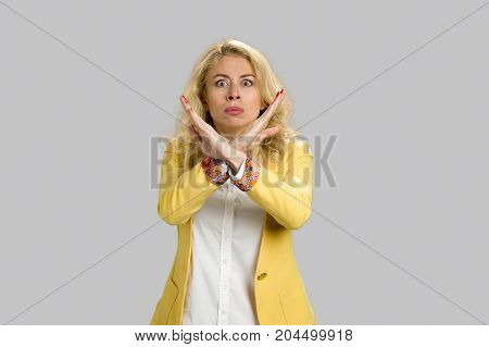 Young expressive woman making stop gesture. European blonde woman showing denial with no on her hand with blank copy space.
