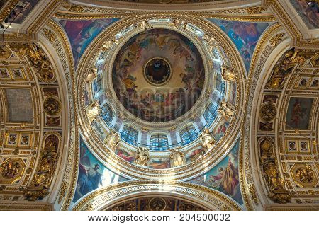 ST PETERSBURG RUSSIA - AUGUST 15 2017. Ceiling ornated with sculptures and Bible paintings in the interior of the St Isaac Cathedral in St Petersburg Russia
