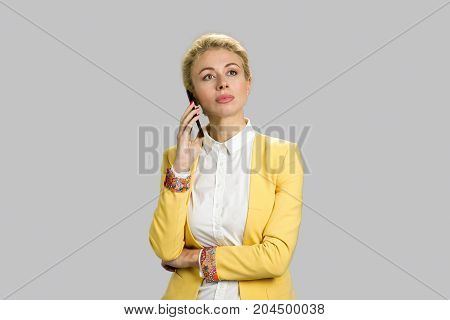 Attractive young manager talking on smartphone. Beautiful business lady in yellow jacket and white shirt holding mobile phone on grey background.